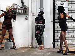 Tied to a post and wrapped in cling film the slave must endure a whipping from two Mistresses.