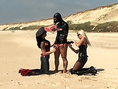 A deserted beach, two rubber clad Mistresses and a willing slave for them to toy with.