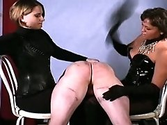 Two of four mistresses simultaneously paddle a male slave brutally; then one whips his raw buns while another kicks him in the balls